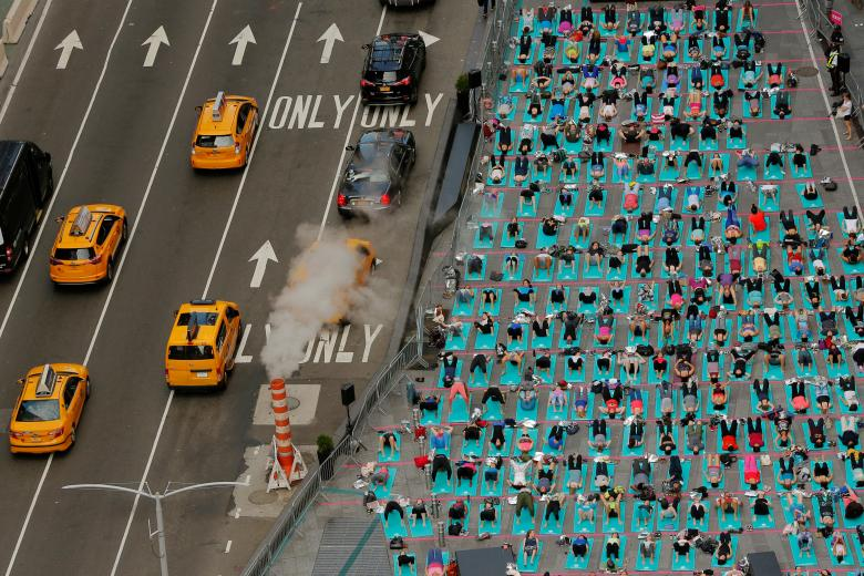 People participate in a yoga class during an annual Solstice event in the Times Square district of New York. REUTERS/Lucas Jackson