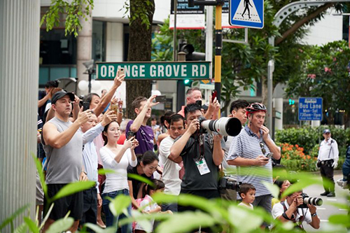 Photographers and members of the public getting ready to snap pictures of Mr Kims motorcade at the junction of Orange Grove and Orchard roads. Over the past days, crowds have gathered around the St Regis and Shangri-La, where the leaders stayed.PHOTO: LIN ZHAOWEI FOR THE STRAITS TIMES