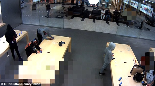 Brazen: The men first walked into the shop and browsed before snatching the phones and making a run for it